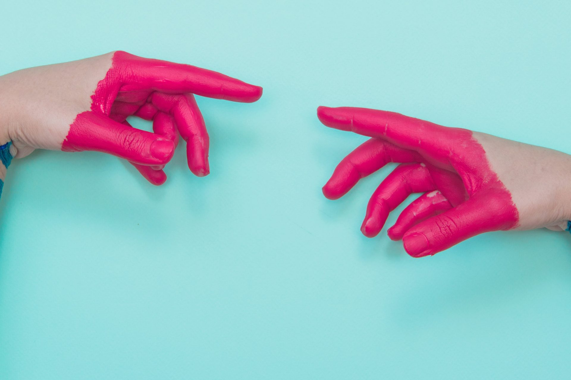 Two painted hands try to reach each other's fingers. Creative connecting conception